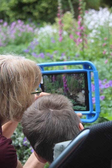 Child with carer taking photos of garden using the iPad